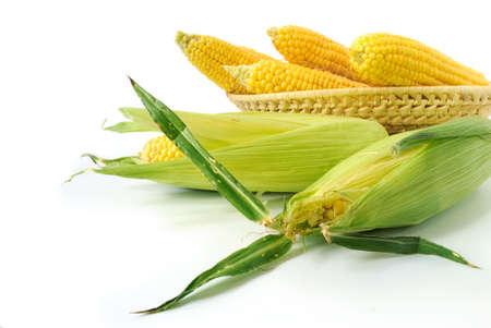 mais: Fresh corn cobs in a basket on white background Stock Photo