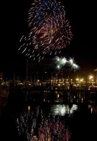 Firework explode over the Sandy Hook Bay Marina in Atlantic Highlands, NJ, USA Bursts are reflected in the ocean.  Stock Photo