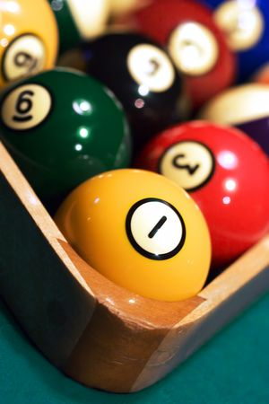 Close up of Racked pool balls with the tight focus on a 1-ball. Picture was taken in low light, to preserve the real billiard light