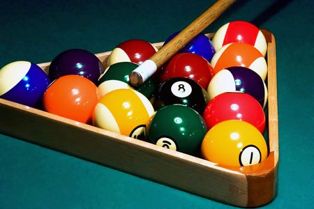 15 ball rack of billiard balls, and a cue stick on the green billiard table. Picture was taken in low light, to preserve the real billiard light