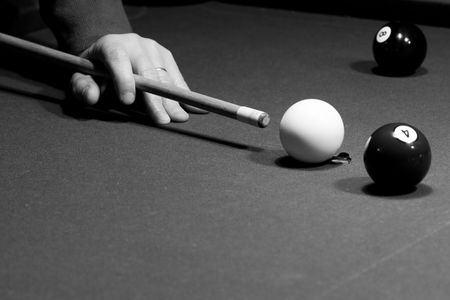 Man is aiming the billiard shot - cue is in his hand, and the balls are on the table.Picture was taken in low light, to preserve the real billiard light