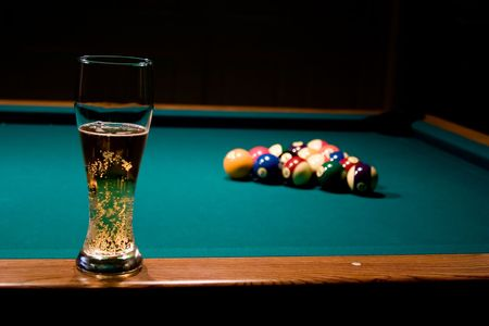 Glass of refreshing beer on the billiard table with the racked billiard balls