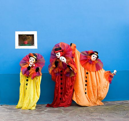 Three white clowns in the yellow, red, and orange Traditional Clothing are performing in front of blue wall with small window