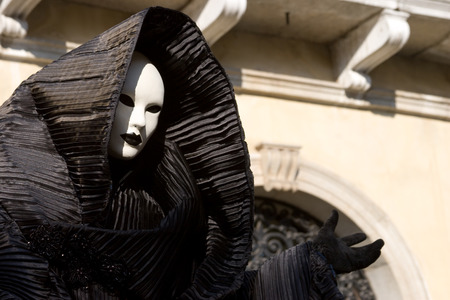 Figure in the black costume with hood, and white mask, gesturing. Venice. Masquerade