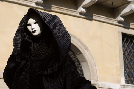 Figure in the black costume with hood, and white mask. Venice. Masquerade.