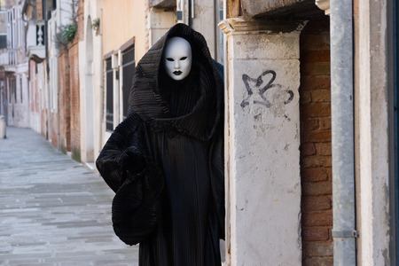 Figure in the black costume with hood, and white mask near the wall on the street. Venice. Masquerade.