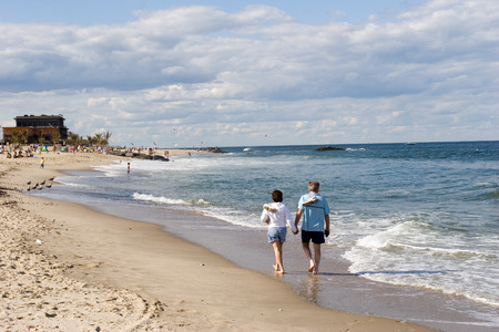 Couple walking along the waters edge, relaxing after jogging, taking their sneakers off