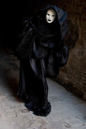 venice:  Figure in the black costume with hood, and white mask, gesturing. Venice. Masquerade