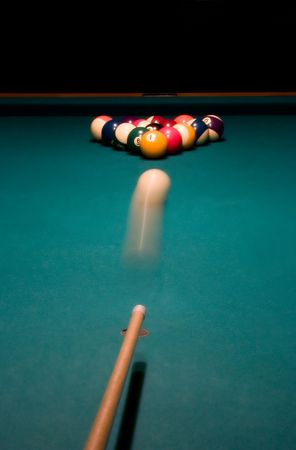 Shooting the white ball to break the racked billiard balls.Focus is on the racked balls. motion blur.