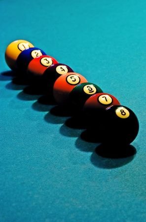 Eight billiard balls in the row arranged in order on the green pool tableDOF on the ball number 6, taken with directional light to give a deep shadow.