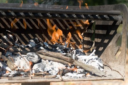 chargrill: Campground Barbecue Grill with Flames coming off of burning charcoals and wood.