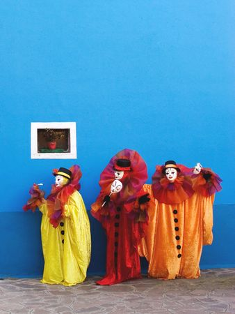 comedian: Three white clowns in the yellow, red, and orange traditional theatrical clowns costumes are performing in front of blue wall with small window