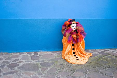 Small orange Clown in white mask, and top hat sitting in front of the blue wall - alone