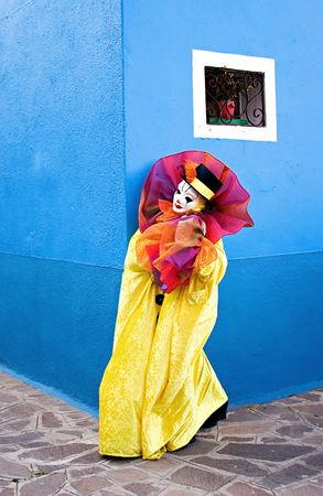 Clown in white mask, and bright yellow clowns theatrical costume looking at the corner of the blue wall. Stock Photo
