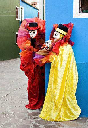 Two clowns in white masks, and traditional red and yellow clowns theatrical costumes surprisingly meet at the corner Stock Photo