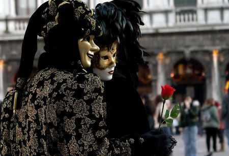 Couple dressed for Carnival in black and gold masks with the red rose posing on Saint Marks Square in Venice, Italy.