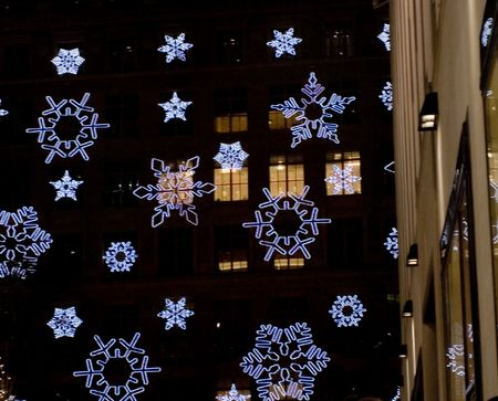 Holiday light display at Rockefeller Center - Christmas Snowflakes lighting with buildings night windows on the background. Stock Photo