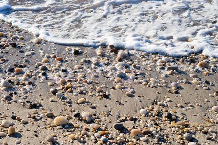 Pebbles and Sand on the waters edge at ebb tide. Atlantic Ocean coastline. Stock Photo