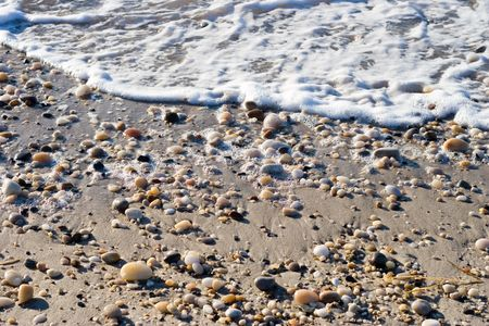 waters  edge: Pebbles and Sand on the waters edge at ebb tide. Atlantic Ocean coastline. Stock Photo