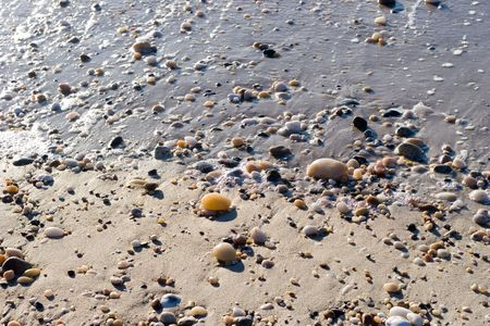 Pebbles and Sand on the waters edge at ebb tide Stock Photo