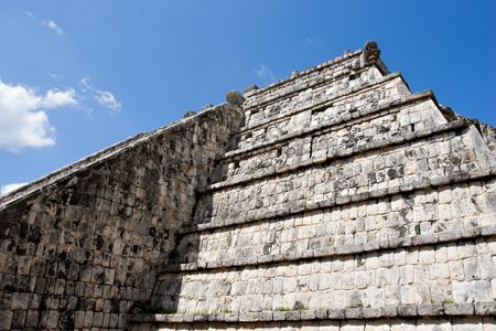 Wall of Ancient Mayan Pyramid at Chichen Itza on the blue sky. Chichen Itza in the Yucatan was a Maya city and one of the greatest religious center and remains today one of the most visited archaeological sites