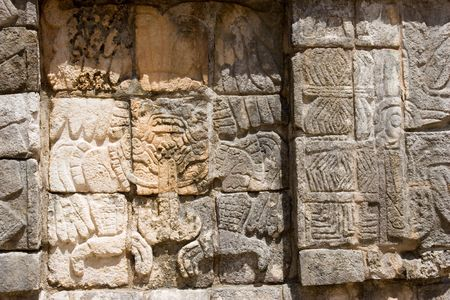 Mayan figures carved into the old stone wall at Chichen Itza. Mexico