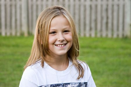 A portrait of an adorable girl, 8, with a pretty smile, looking into camera.