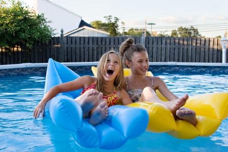 女の子一緒に浮かんで、笑って、スイミング プールで楽しんでいます。 写真素材