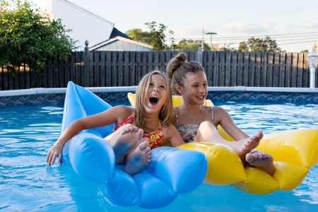 inflatable: Girls floating together, laughing, and having fun in the swimming pool.