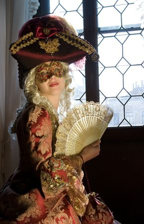 Woman in renaissance mask with fan, dressed in period costume with lace and jewelry, and tricorn hat, looking tempting in front of big window