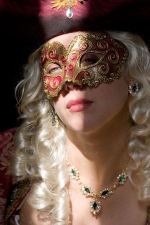 Tempting woman in renaissance mask with emerald necklace and earrings, - face is partially on the light, and partially in shadow