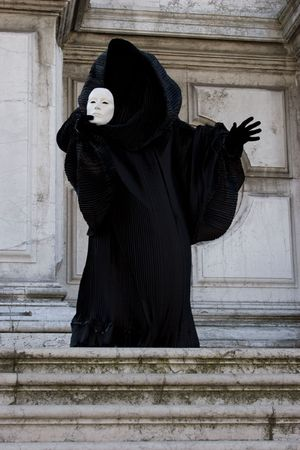 disclose: Black figure staying on the steps, holding in the hand white face mask. Venice. Masquerade Stock Photo
