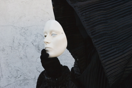 Black figure in the hood, taking off white face mask. Venice. Masquerade Imagens
