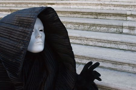 Figure in the black costume with hood, and white mask, gesturing on the stairs. Venice. Masquerade