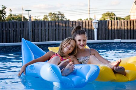 Girls floating together, resting, and having fun in the swimming pool.