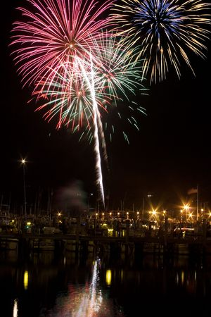 4th of July firework explodes over the Sandy Hook Bay Marina in Atlantic Highlands, NJ, USA Bursts are reflected in the ocean. Stock Photo