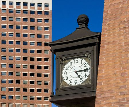Old style iron street clock mounted on wall of brick skyscraper in New York downtown financial district (Wall Street) on the blue sky background. The time is five fifteen. Stock Photo - 2824025