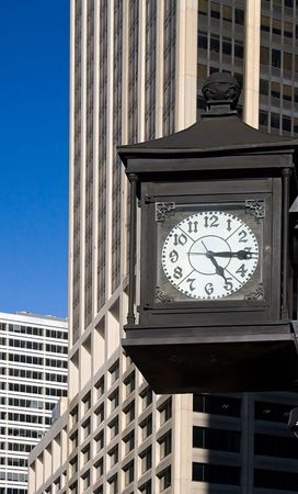 Old-fashioned iron street clock mounted on the wall in front of modern  skyscrapers in New York downtown financial district (Wall Street) on the blue sky background.  The time is fifteen after five. Stock Photo - 2824022