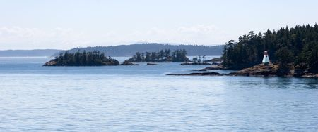 Lighthouse on the rocky wooded island. Gulf Islands. British Columbia.