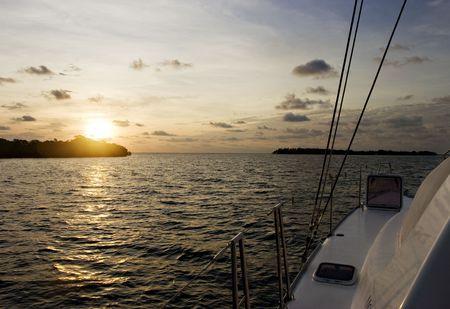 Boat sailing at sunrise between islands. Caribbean Dawn. Crawl Caye, Belize.