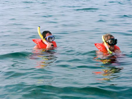 Two men  in the life vest and diving mask with snorkel swiming in the ocean