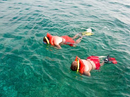 Two men  in the life vest snorkeling in the Turquoise Water on Carribean