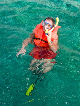 Man in he life vest and diving mask with snorkel in the ocean