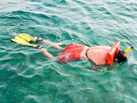 Man in the life vest snorkeling in the Turquoise Water on Carribean Stock Photo