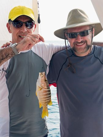 two adult mature men holding up the yellow snapper they just caught from the ocean  Stock Photo