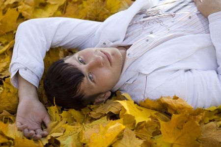 beauty man laying on falling leaves photo