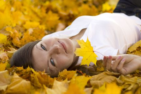 smiling woman laying on falling leaves photo