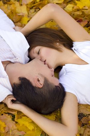 women kissing: kissing couple in autumn park
