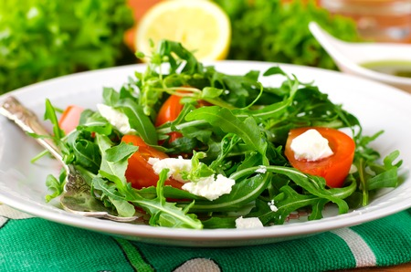 salads: Green salad with arugula, tomato and feta cheese. Italian cuisine Stock Photo