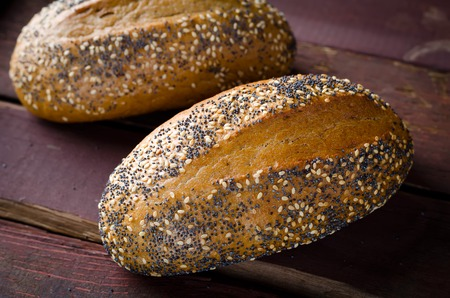 poppy seeds: Freshly baked small breads with sesame and poppy seeds. Selective focus